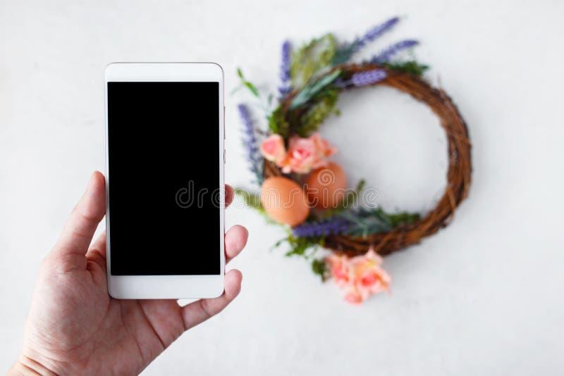 Женская рука с венком с яркими цветками весны, гнездом пасхи фотоснимков телефона с пасхальными яйцами стоковые изображения