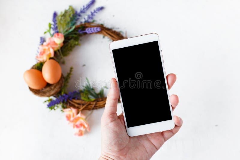 Женская рука с венком с яркими цветками весны, гнездом пасхи фотоснимков телефона с пасхальными яйцами стоковые фотографии rf