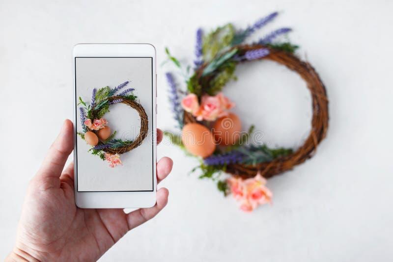 Женская рука с венком с яркими цветками весны, гнездом пасхи фотоснимков телефона с пасхальными яйцами стоковые фото