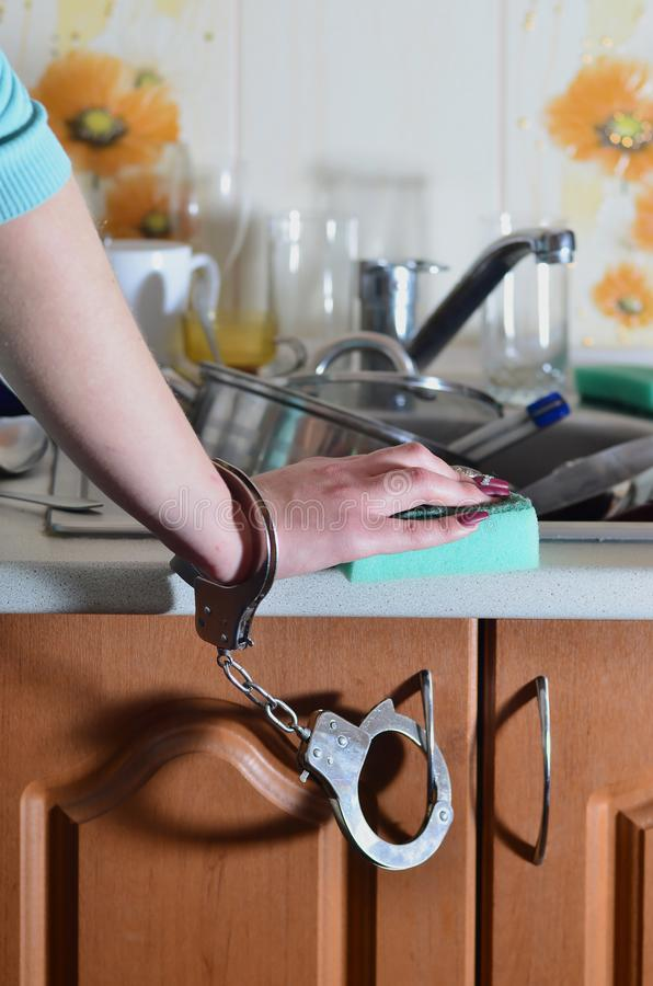 Женская рука с губкой, надеванной наручники к счетчику кухни с a стоковые фото