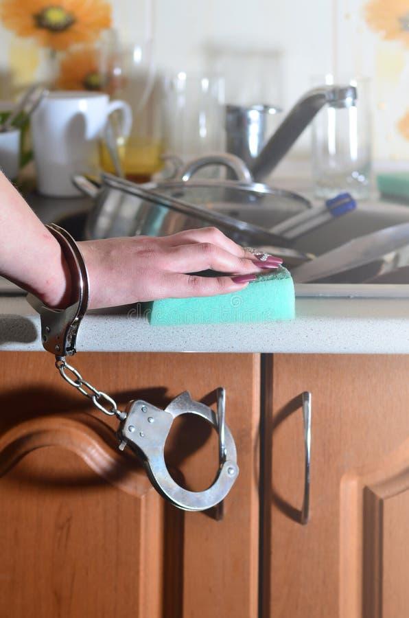 Женская рука с губкой, надеванной наручники к счетчику кухни с a стоковое изображение rf
