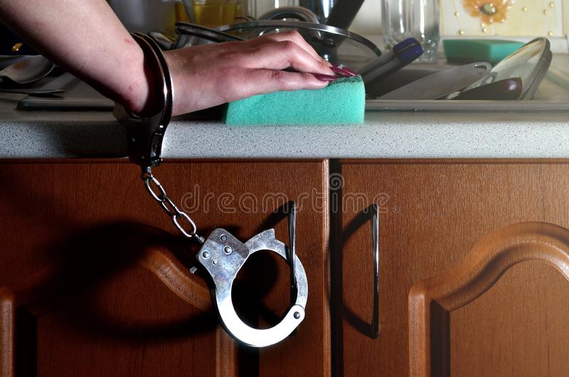 Женская рука с губкой, надеванной наручники к счетчику кухни с a стоковое фото