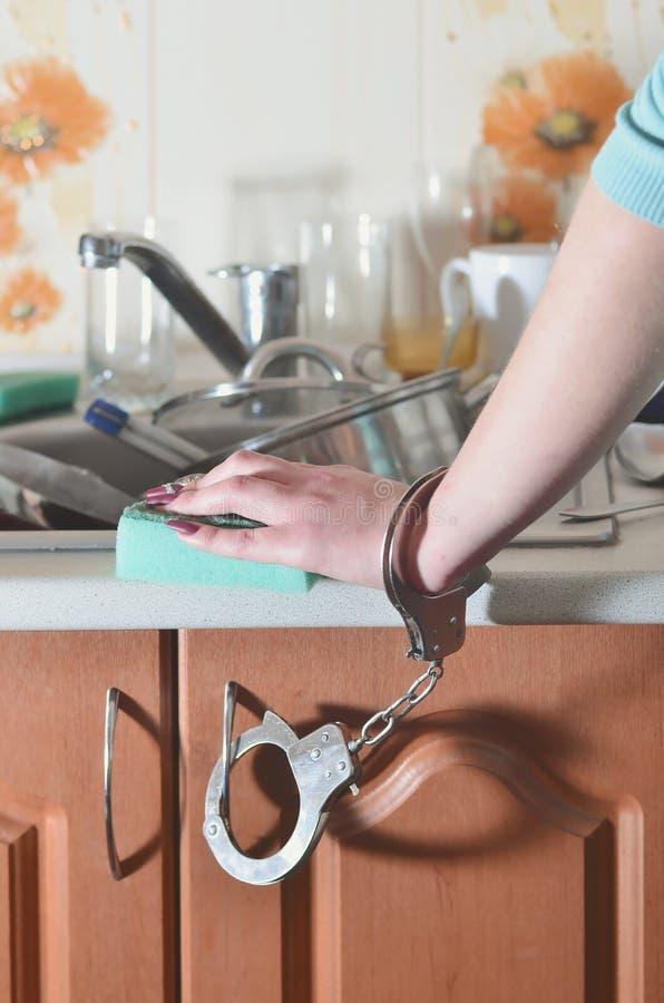 Женская рука с губкой, надеванной наручники к счетчику кухни с a стоковая фотография