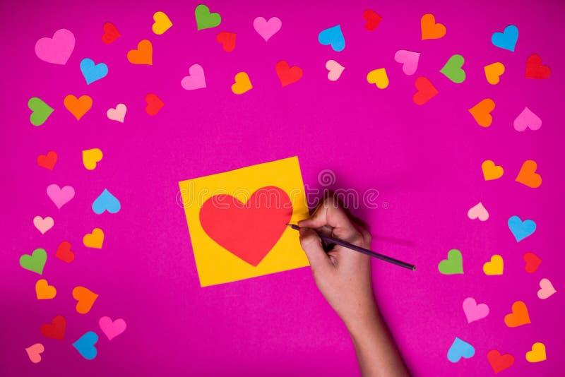 Женская рука с карандашем пишет на поздравительной открытке в форме сердца стоковые фото