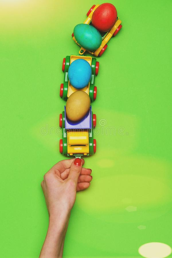 Женская рука с красочными пасхальными яйцами в игрушке автомобиля грузовика стоковые фото