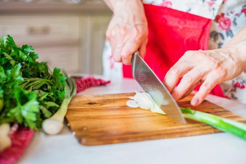 Женская рука с лук-пореем отрезков ножа зеленым в кухне Варить овощи стоковые изображения