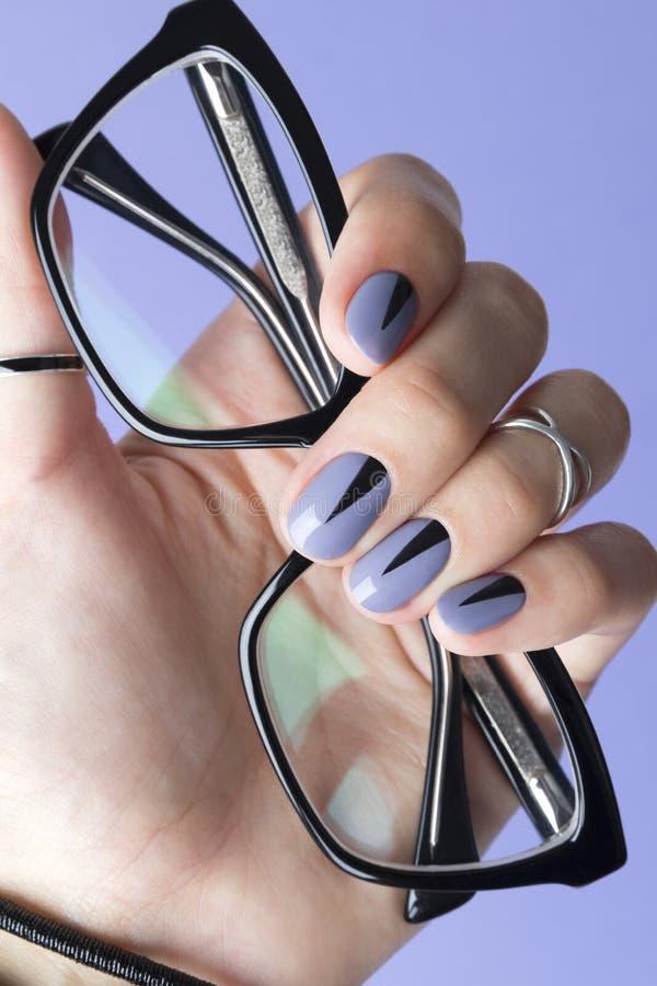 Женская рука с модным маникюром держа черные стекла стоковое фото rf