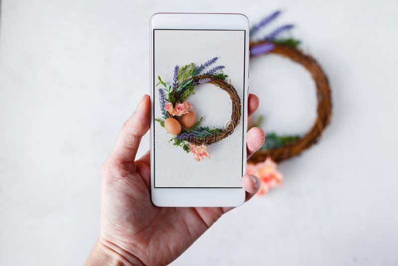 Женская рука с телефоном фотографирует венок с яркими цветками весны, гнездо пасхи с пасхальными яйцами стоковая фотография