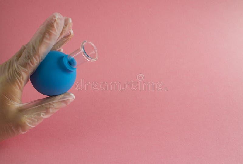 Женская рука с французским маникюром в перчатке медицины держит голубой косметический медицинский опарник для массажа вакуума лиц стоковые изображения