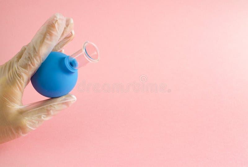 Женская рука с французским маникюром в перчатке медицины держит голубой косметический медицинский опарник для массажа вакуума лиц стоковое изображение rf