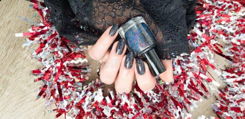Женская рука с черными маникюром и бутылкой стоковая фотография rf