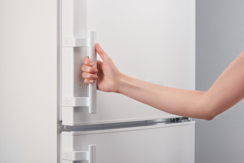 Женская ручка удерживания руки белой двери холодильника стоковое изображение