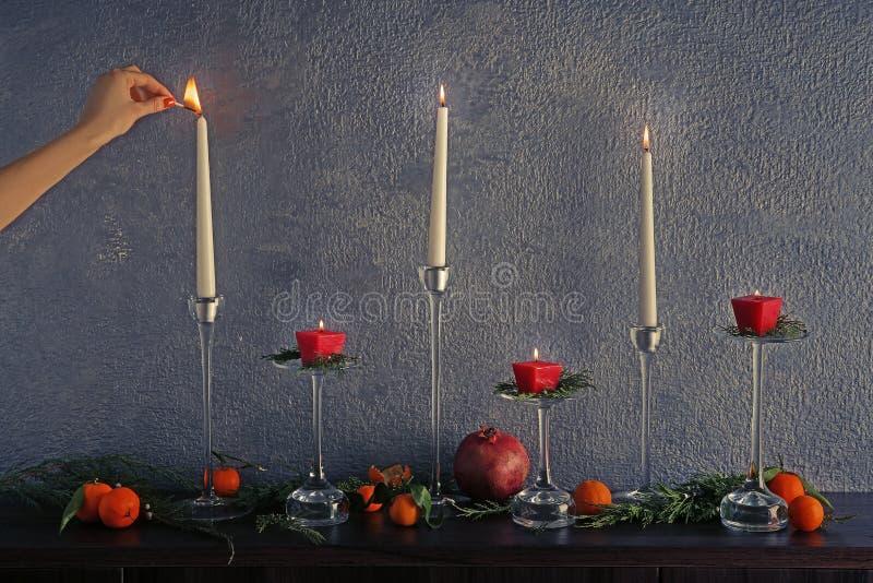 Женская свеча освещения руки на таблице с плодоовощами стоковая фотография rf
