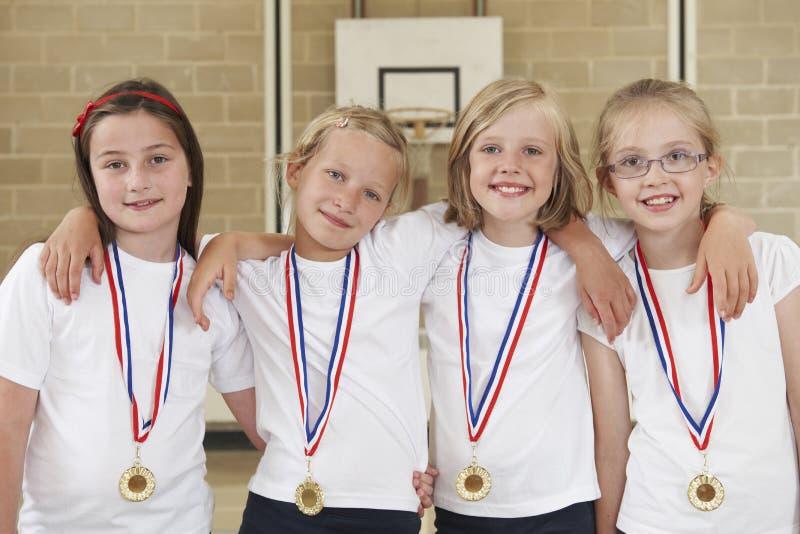 Женская спортивная команда школы в спортзале с медалями стоковое фото