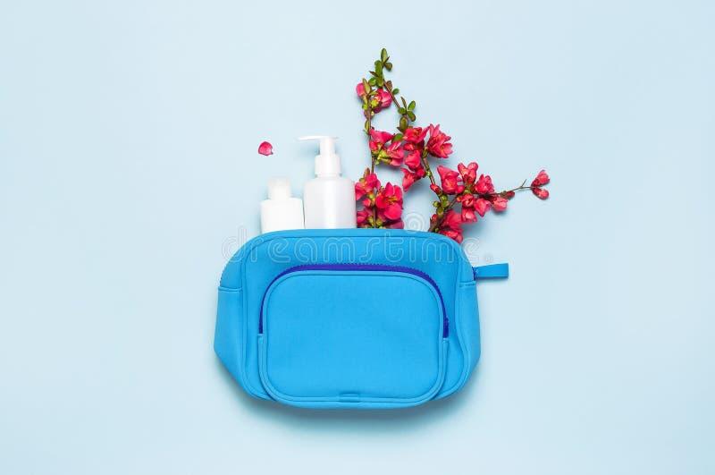 Женская сумка косметик, косметические продукты, белые косметические контейнеры, розовые цветки на экземпляре пастельного голубого стоковое фото rf