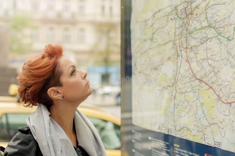 Женская туристская смотря общественная карта улицы стоковое фото rf