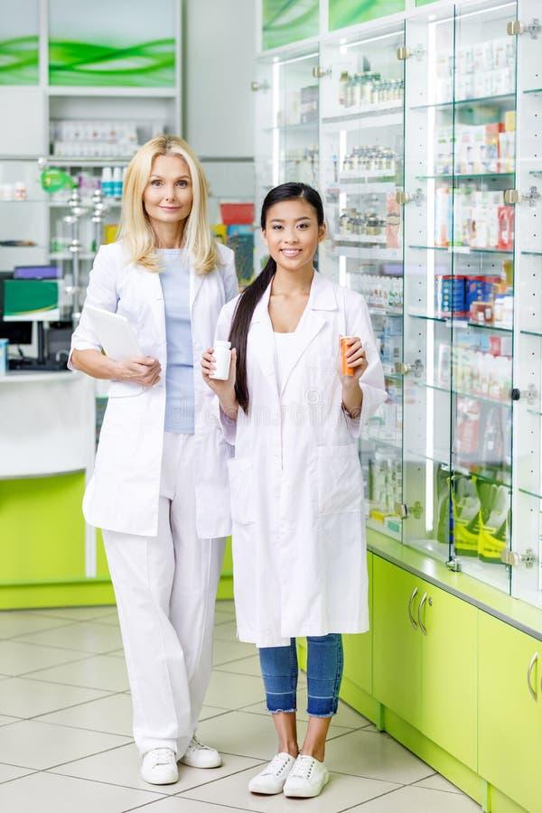 женские аптекари с цифровой таблеткой и лекарства усмехаясь на камере стоковое фото rf