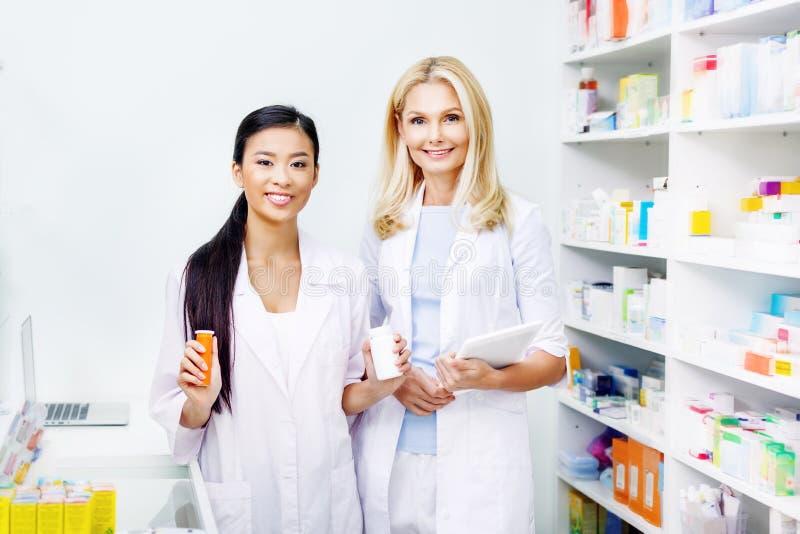 женские аптекари с цифровыми таблеткой и лекарством усмехаясь на камере стоковые изображения