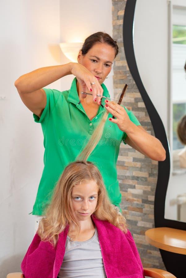 Женские волосы вырезывания парикмахера белокурой девушки стоковые фотографии rf