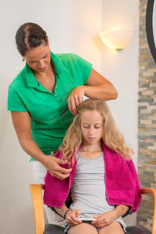 Женские волосы вырезывания парикмахера белокурой девушки стоковые изображения rf