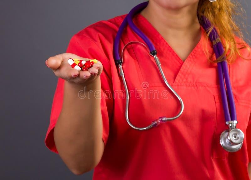 Женские доктор или нюна при стетоскоп держа пилюльки в ее ha стоковые изображения