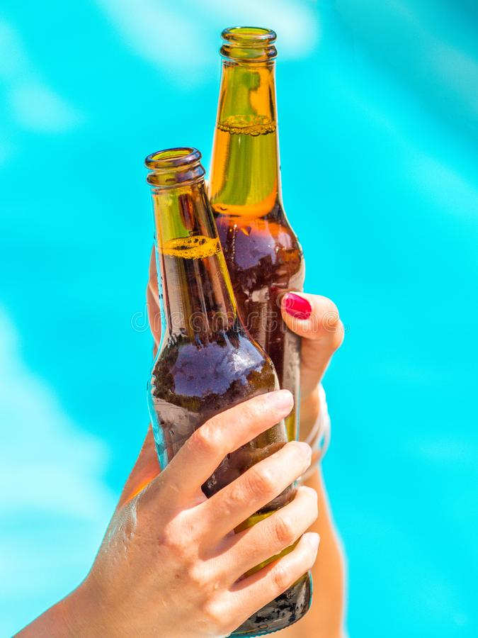 Женские друзья веселят clinking бутылки пива в их руках рядом с бассейном открытого моря стоковая фотография rf