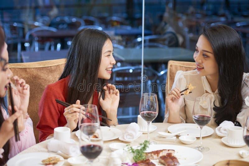 Женские друзья злословя на обедающем стоковые изображения rf
