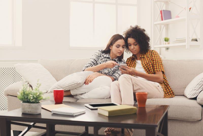 Женские друзья используя smartphone дома стоковые изображения