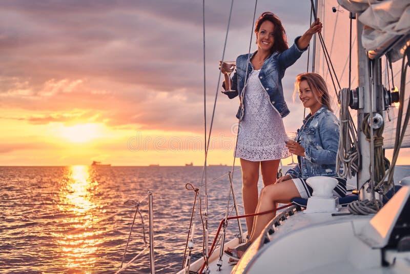 Женские друзья ослабляя на яхте с стеклами вина в руках, во время захода солнца в открытом море стоковая фотография rf