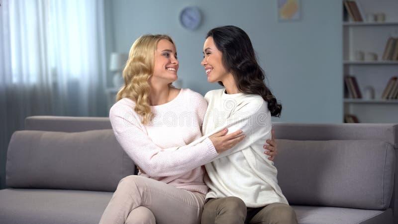 Женские друзья сидя на софе дома, обнимая и примиряя после ссоры стоковое фото