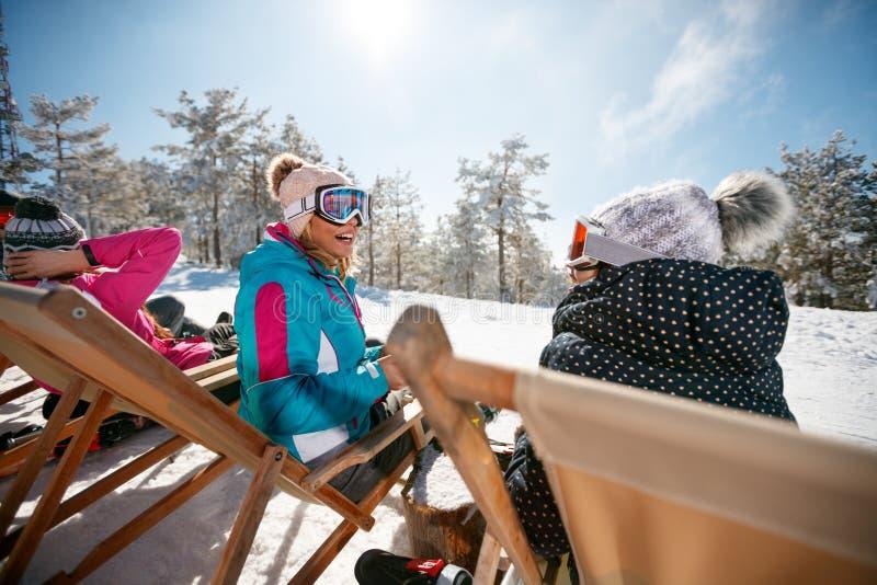 Женские друзья сидя с шезлонгами в горах зимы bac стоковые фотографии rf