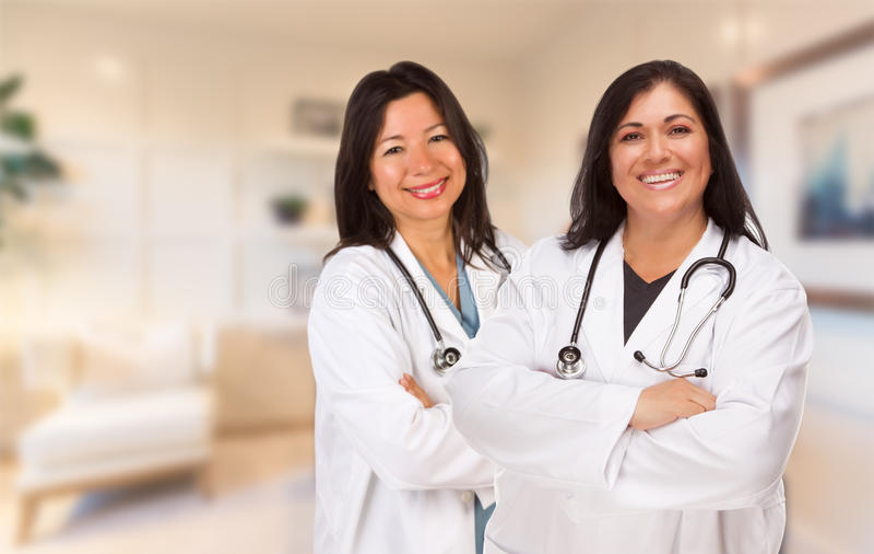 Женские испанские доктора или медсестры стоя в офисе стоковые изображения rf