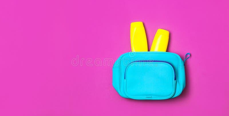 Женские косметики кладут в мешки, косметические продукты, желтая бутылка солнцезащитного крема и лосьон sunblock, брызги на яркой стоковая фотография rf