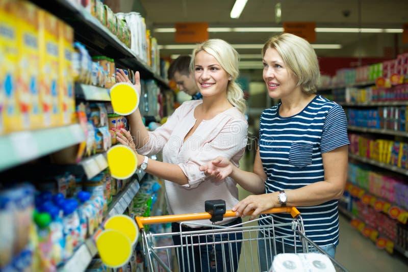 Женские клиенты выбирая младенческую еду стоковое изображение rf