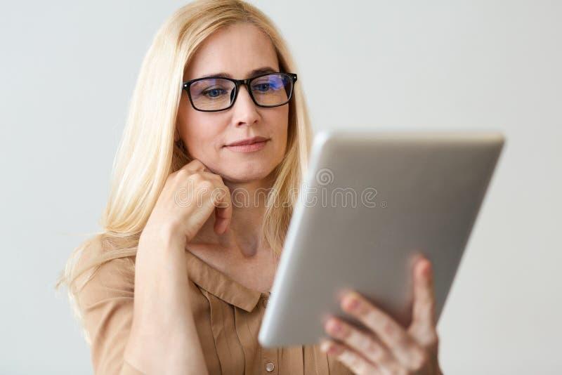 Женские новости чтения финансиста на планшете онлайн стоковые изображения