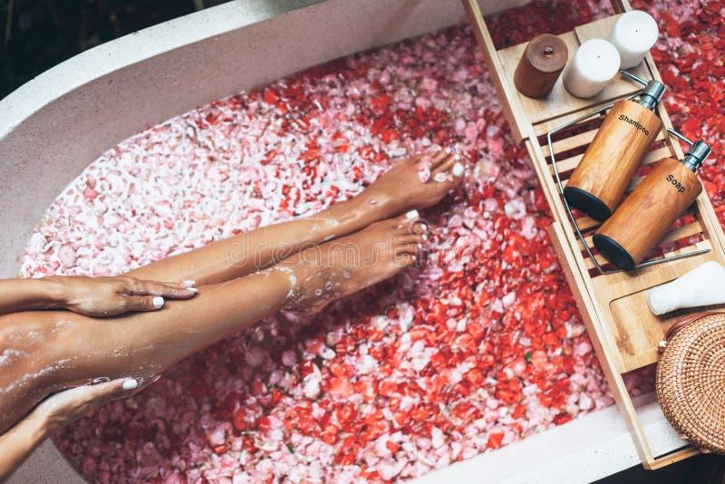 Женские ноги в ванне с лепестками цветка и продуктами красоты на деревянном подносе стоковая фотография