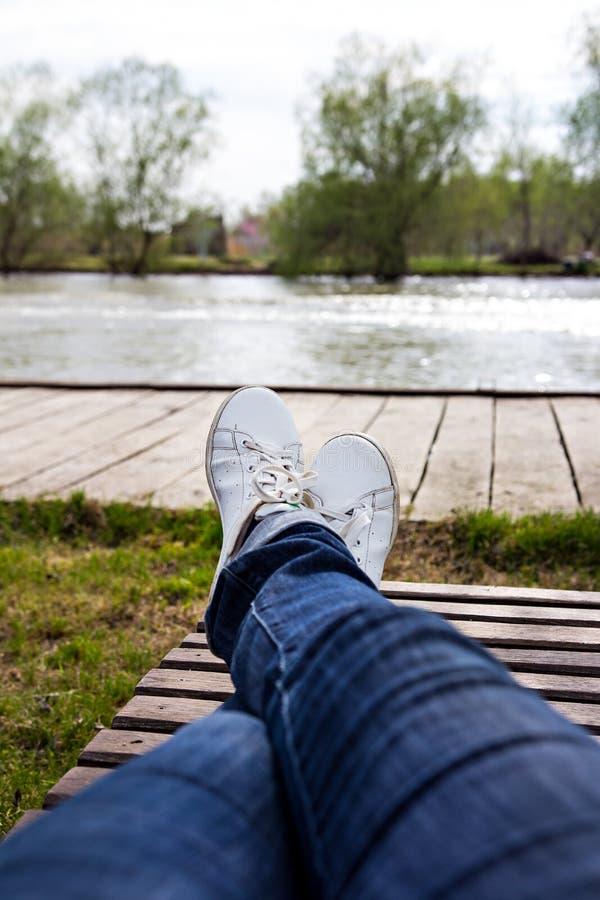 Женские ноги в джинсах и белых тапках лежат на deckchair стоковое фото