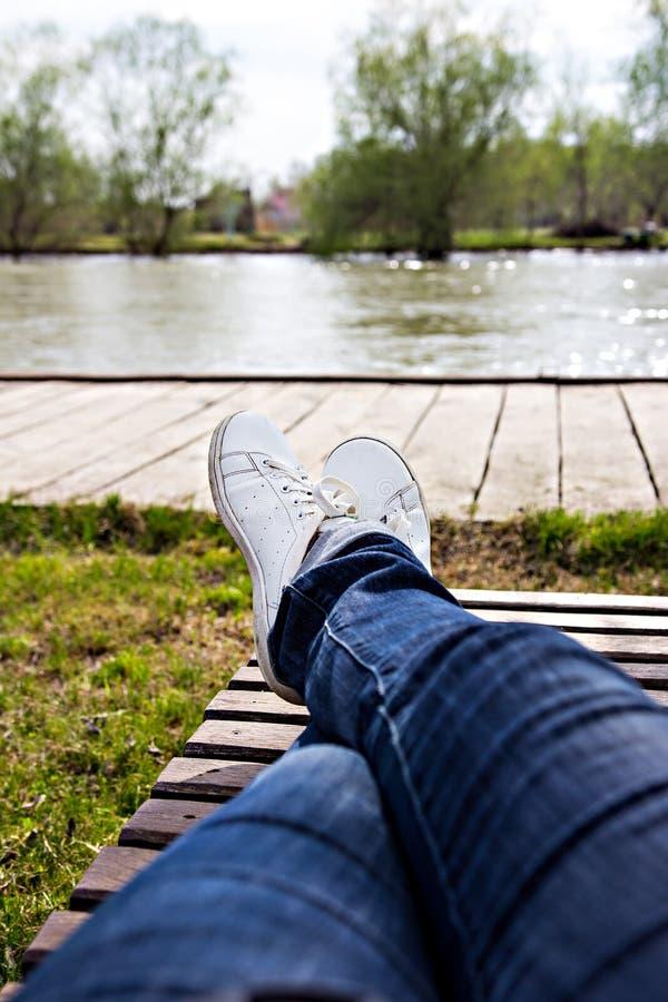 Женские ноги в джинсах и белых тапках лежат на deckchair стоковая фотография