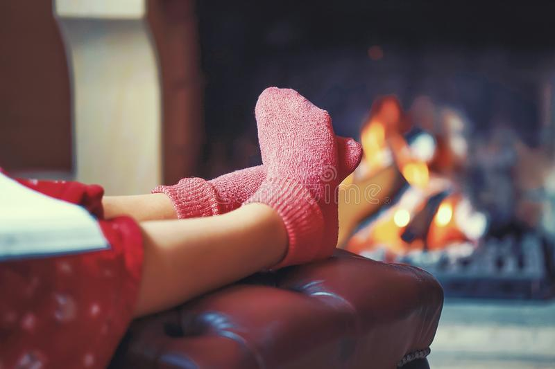 Женские ноги в носках около камина стоковые изображения
