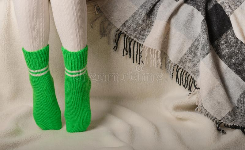 Женские ноги в теплых белых связанных колготках и зеленые носки на wh стоковые изображения