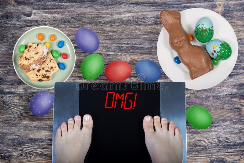 Женские ноги в цифровых масштабах с omg знака! окруженный тортом пасхи еды пасхи, зайчик пасхи шоколада, покрасил яйца стоковые изображения rf