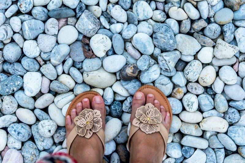 Женские ноги крупного плана камешков стоковые фото