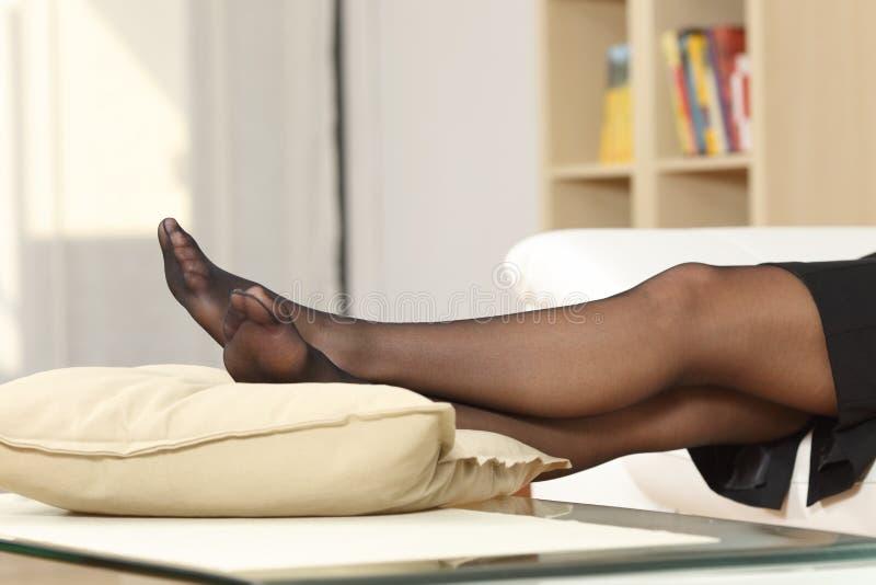 Женские ноги отдыхают на диване дома стоковая фотография