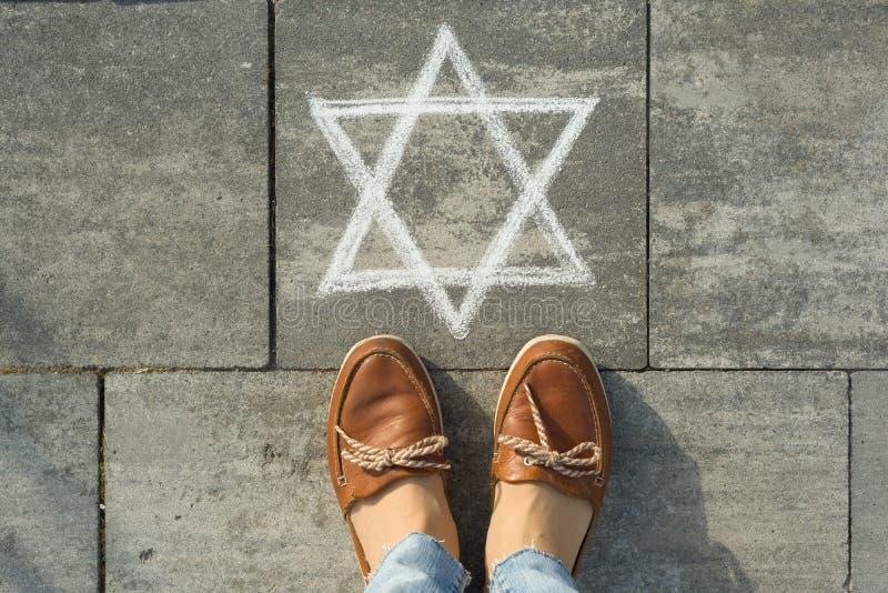 Женские ноги с абстрактным изображением 6 остроконечных звезд, написанным на сером тротуаре стоковое изображение rf