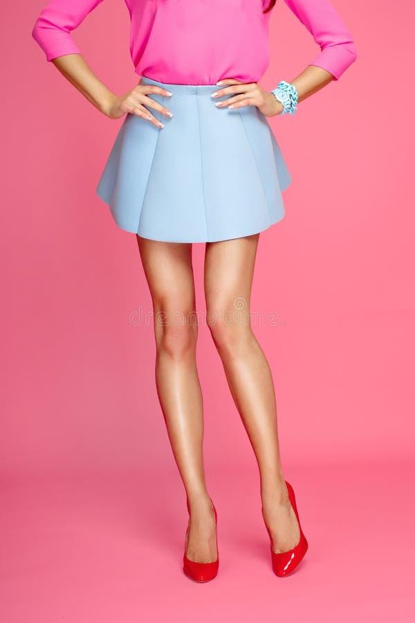 Женские ноги с красными пятками и юбкой краткости голубой стоковая фотография rf