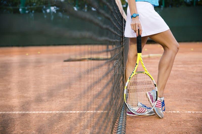 Женские ноги с ракеткой стоковая фотография rf