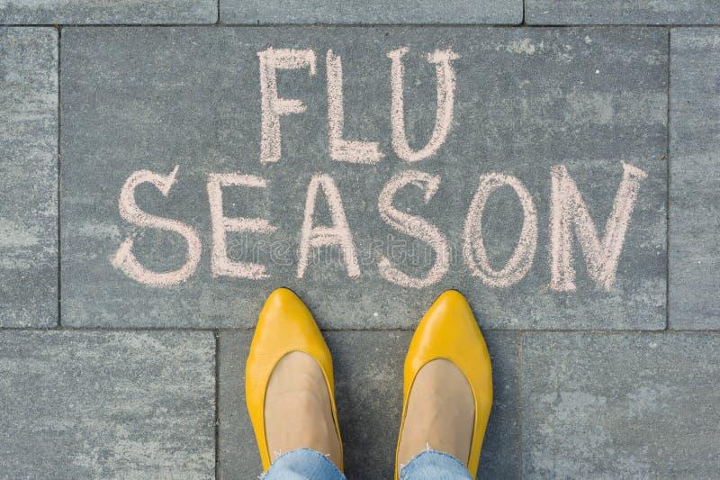 Женские ноги с сезоном гриппа текста написанным на сером тротуаре стоковое фото rf