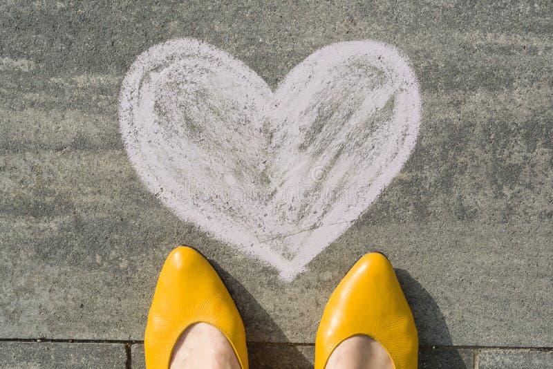 Женские ноги с сердцем символа покрашенным на асфальте стоковое фото rf