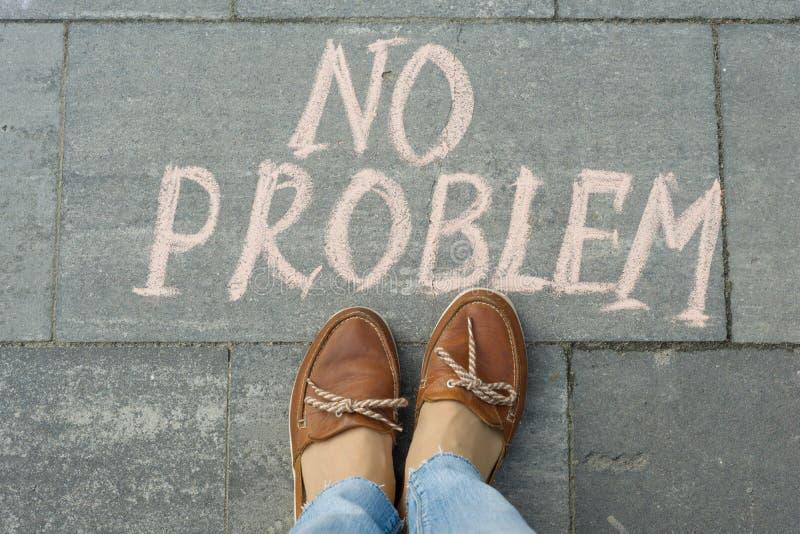 Женские ноги с текстом отсутствие проблемы написанной на сером тротуаре стоковая фотография rf