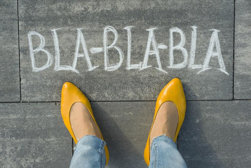 Женские ноги с bla-bla-bla текста написанным на сером тротуаре стоковая фотография rf